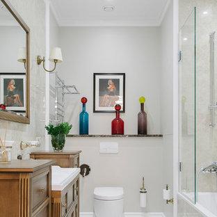 Неиссякаемый источник вдохновения для домашнего уюта: большая главная ванная комната в стиле современная классика с фасадами с утопленной филенкой, фасадами цвета дерева среднего тона, ванной в нише, инсталляцией, серыми стенами, монолитной раковиной и белым полом