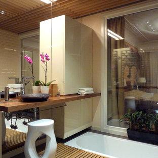 На фото: ванная комната в восточном стиле с бежевой плиткой, керамической плиткой, бежевыми стенами, полом из цементной плитки, столешницей из дерева и настольной раковиной с