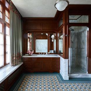 Пример оригинального дизайна: ванная комната в классическом стиле с фасадами с утопленной филенкой, темными деревянными фасадами, душем в нише, серой плиткой, коричневыми стенами, врезной раковиной, разноцветным полом, белой столешницей и душем с распашными дверями
