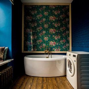 Ejemplo de cuarto de baño con ducha, ecléctico, con bañera exenta, paredes azules y suelo de madera en tonos medios