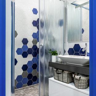 На фото: маленькая ванная комната в скандинавском стиле с синей плиткой, белой плиткой, керамической плиткой, душевой кабиной, столешницей из искусственного камня, душем с раздвижными дверями, плоскими фасадами, белыми фасадами, душем в нише, настольной раковиной и серым полом с