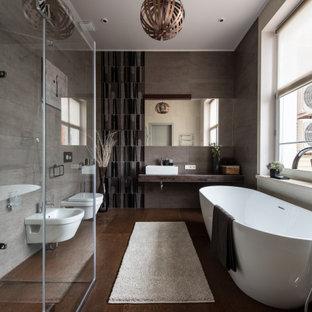 Стильный дизайн: главная ванная комната в современном стиле с отдельно стоящей ванной, биде, настольной раковиной и коричневым полом - последний тренд
