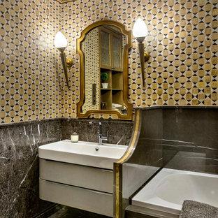 Новые идеи обустройства дома: главная ванная комната среднего размера в викторианском стиле с гидромассажной ванной, инсталляцией, мраморной плиткой, мраморным полом, серым полом, плоскими фасадами, белыми фасадами, желтой плиткой, серой плиткой, душем над ванной, монолитной раковиной и шторкой для душа