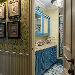Immagine di una grande stanza da bagno mediterranea con ante a persiana, ante blu, doccia alcova, piastrelle in gres porcellanato, pareti gialle, pavimento in gres porcellanato, lavabo sottopiano, top in marmo, pavimento multicolore e top beige