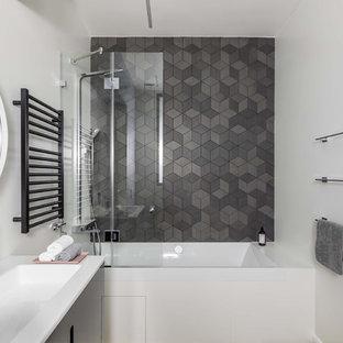Пример оригинального дизайна: главная ванная комната среднего размера в скандинавском стиле с плоскими фасадами, черными фасадами, накладной ванной, душем над ванной, серой плиткой, керамической плиткой, белыми стенами и монолитной раковиной