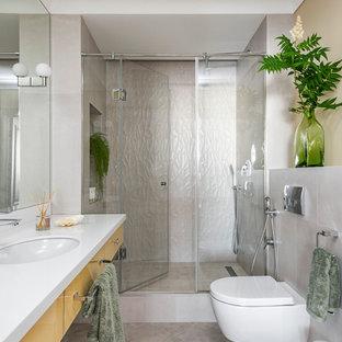 Создайте стильный интерьер: ванная комната среднего размера в современном стиле с плоскими фасадами, желтыми фасадами, душем в нише, инсталляцией, душевой кабиной, врезной раковиной, столешницей из искусственного камня, душем с распашными дверями, белой столешницей, серой плиткой и серым полом - последний тренд