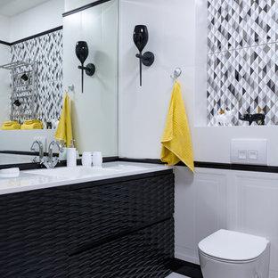 Пример оригинального дизайна: ванная комната в скандинавском стиле с черными фасадами, полновстраиваемой ванной, инсталляцией, черно-белой плиткой, керамической плиткой, белыми стенами, полом из керамической плитки, монолитной раковиной и белым полом