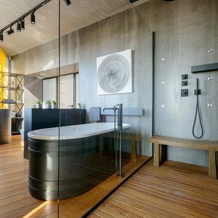 Удачное сочетание для дизайна помещения: главная ванная комната в современном стиле с душем без бортиков, серыми стенами, коричневым полом, отдельно стоящей ванной, паркетным полом среднего тона, раковиной с пьедесталом и открытым душем - самое интересное для вас