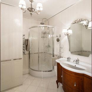Выдающиеся фото от архитекторов и дизайнеров интерьера: ванная комната среднего размера в классическом стиле с угловым душем, белой плиткой, белыми стенами, полом из керамической плитки, душевой кабиной, монолитной раковиной, фасадами цвета дерева среднего тона и душем с раздвижными дверями