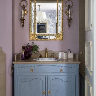 На фото: ванная комната в стиле неоклассика (современная классика) с фасадами с утопленной филенкой, синими фасадами, фиолетовыми стенами, накладной раковиной, бежевым полом и бежевой столешницей