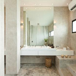 На фото: ванная комната в современном стиле с плоскими фасадами, белыми фасадами, серыми стенами, бетонным полом, раковиной с несколькими смесителями, серым полом и белой столешницей с