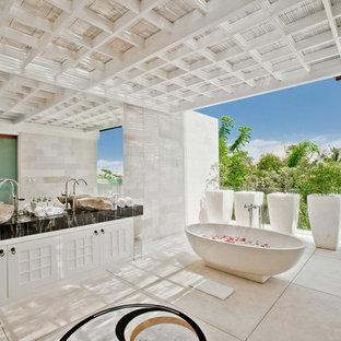 На фото: главная ванная комната в морском стиле с фасадами с утопленной филенкой, белыми фасадами, отдельно стоящей ванной, белыми стенами, черной столешницей, серой плиткой, настольной раковиной и бежевым полом