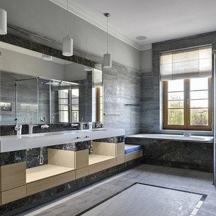Идея дизайна: главная ванная комната в современном стиле с плоскими фасадами, накладной ванной, душем без бортиков, серой плиткой, серыми стенами, монолитной раковиной, серым полом и светлыми деревянными фасадами