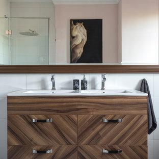 Создайте стильный интерьер: ванная комната в современном стиле с плоскими фасадами, темными деревянными фасадами, угловым душем, белой плиткой, розовыми стенами, раковиной с несколькими смесителями и разноцветным полом - последний тренд