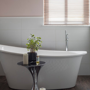 Стильный дизайн: главная ванная комната в современном стиле с отдельно стоящей ванной и розовыми стенами - последний тренд