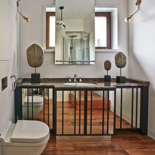 Immagine di una stanza da bagno con doccia design con WC sospeso, pareti bianche, pavimento in legno massello medio, lavabo sottopiano e pavimento arancione
