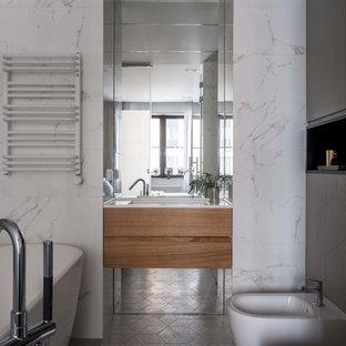 Идея дизайна: главная ванная комната в современном стиле с отдельно стоящей ванной, плоскими фасадами, фасадами цвета дерева среднего тона, биде, белой плиткой, керамогранитной плиткой, серым полом, белой столешницей, серыми стенами и монолитной раковиной
