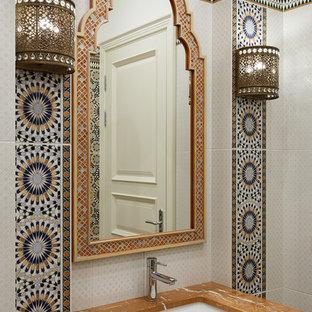 Идея дизайна: ванная комната в восточном стиле с белыми фасадами, разноцветной плиткой, врезной раковиной и коричневой столешницей