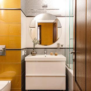 Свежая идея для дизайна: главная ванная комната в современном стиле с плоскими фасадами, белыми фасадами, ванной в нише, душем над ванной, инсталляцией, белой плиткой, желтой плиткой, серой плиткой, монолитной раковиной и коричневым полом - отличное фото интерьера