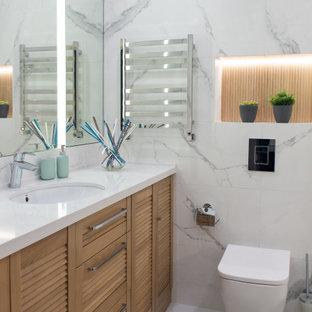 Стильный дизайн: маленькая ванная комната в современном стиле с фасадами с филенкой типа жалюзи, фасадами цвета дерева среднего тона, инсталляцией, серой плиткой, керамогранитной плиткой, врезной раковиной, серым полом, белой столешницей, тумбой под одну раковину и встроенной тумбой - последний тренд