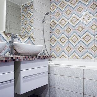 Modelo de cuarto de baño infantil, bohemio, grande, con armarios con paneles lisos, bañera encastrada sin remate, ducha empotrada, sanitario de pared, baldosas y/o azulejos rosa, baldosas y/o azulejos en mosaico, paredes blancas, suelo con mosaicos de baldosas, lavabo encastrado, encimera de vidrio, suelo violeta, ducha con cortina y encimeras moradas