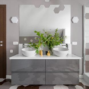 На фото: ванная комната в современном стиле с плоскими фасадами, серыми фасадами, разноцветной плиткой, серыми стенами, душевой кабиной, настольной раковиной, разноцветным полом и белой столешницей