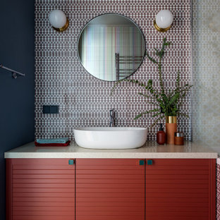Photo of a small contemporary master bathroom in Moscow with multi-coloured tile, ceramic tile, ceramic floors, solid surface benchtops, brown floor, beige benchtops, flat-panel cabinets, red cabinets, black walls and a vessel sink.