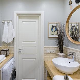 Diseño de cuarto de baño con ducha, bohemio, pequeño, con armarios abiertos, puertas de armario de madera clara, ducha esquinera, sanitario de pared, baldosas y/o azulejos beige, baldosas y/o azulejos de cemento, paredes grises, suelo de azulejos de cemento, lavabo sobreencimera, encimera de madera, suelo multicolor y ducha con puerta corredera