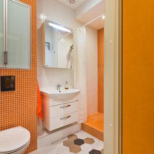 Modelo de cuarto de baño contemporáneo, pequeño, con sanitario de pared, baldosas y/o azulejos naranja, baldosas y/o azulejos en mosaico, suelo de baldosas de cerámica, armarios con paneles lisos, puertas de armario blancas, ducha empotrada y ducha con cortina