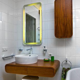 На фото: детская ванная комната в современном стиле с плоскими фасадами, фасадами цвета дерева среднего тона, ванной на ножках, белой плиткой, настольной раковиной, столешницей из дерева, белыми стенами, паркетным полом среднего тона и коричневой столешницей с