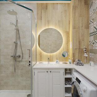 На фото: маленькая ванная комната в современном стиле с фасадами с филенкой типа жалюзи, белыми фасадами, угловым душем, бежевой плиткой, керамогранитной плиткой, бежевыми стенами, душевой кабиной, монолитной раковиной, столешницей из искусственного камня, душем с распашными дверями и белой столешницей с