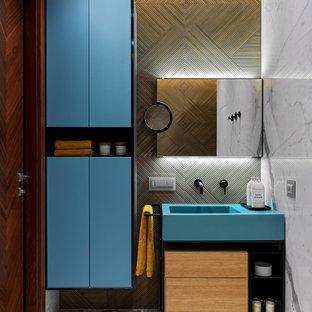На фото: ванная комната в современном стиле с бирюзовыми фасадами, монолитной раковиной, серым полом, тумбой под одну раковину и напольной тумбой с