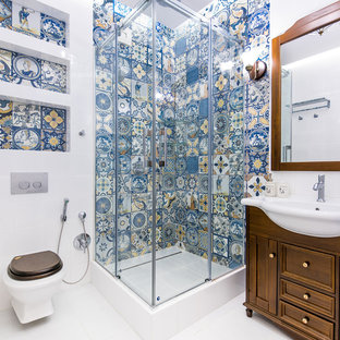 Inspiration for a timeless 3/4 blue tile and white tile white floor bathroom remodel in Other with dark wood cabinets, a wall-mount toilet, furniture-like cabinets and a console sink