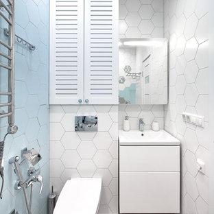 Пример оригинального дизайна: ванная комната в современном стиле с плоскими фасадами, белыми фасадами, инсталляцией, синей плиткой, белой плиткой, монолитной раковиной и серым полом