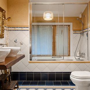 На фото: главная ванная комната в стиле рустика с ванной в нише, душем над ванной, раздельным унитазом, белой плиткой, синей плиткой, желтыми стенами, настольной раковиной, разноцветным полом, столешницей из дерева, душем с раздвижными дверями и коричневой столешницей