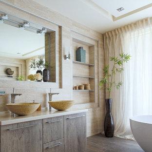 Идея дизайна: главная ванная комната среднего размера в морском стиле с фасадами цвета дерева среднего тона, отдельно стоящей ванной, бежевой плиткой, керамогранитной плиткой, бежевыми стенами, полом из керамогранита, настольной раковиной, столешницей из искусственного камня, бежевой столешницей, плоскими фасадами и коричневым полом