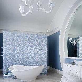 Удачное сочетание для дизайна помещения: ванная комната в стиле современная классика с белыми фасадами, отдельно стоящей ванной, синими стенами, настольной раковиной и бежевым полом - самое интересное для вас
