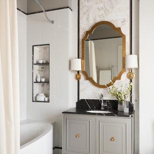 Пример оригинального дизайна интерьера: главная ванная комната в стиле современная классика с белой плиткой, серыми стенами, врезной раковиной, белым полом, серыми фасадами, шторкой для душа, фасадами с утопленной филенкой, отдельно стоящей ванной и душем над ванной