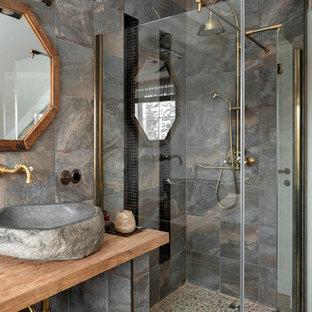Пример оригинального дизайна: ванная комната среднего размера в стиле рустика с угловым душем, серой плиткой, керамогранитной плиткой, полом из керамогранита, настольной раковиной, столешницей из дерева, бежевым полом, душем с распашными дверями, душевой кабиной и коричневой столешницей