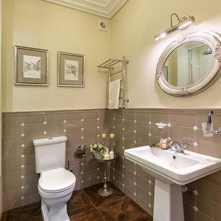 Inredning av ett klassiskt badrum, med en toalettstol med separat cisternkåpa, grå kakel, beige väggar och ett piedestal handfat