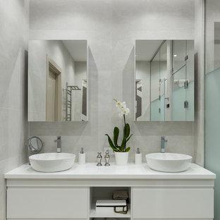 На фото: главная ванная комната в современном стиле с плоскими фасадами, белыми фасадами, серой плиткой, настольной раковиной, серым полом и белой столешницей с