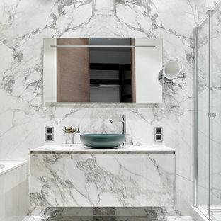 На фото: ванная комната в современном стиле с плоскими фасадами, белыми фасадами, душем в нише, белыми стенами, настольной раковиной, белым полом, белой столешницей, тумбой под одну раковину и подвесной тумбой