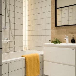 На фото: маленькая главная ванная комната в современном стиле с плоскими фасадами, белыми фасадами, белой плиткой, керамической плиткой, полом из керамической плитки, белым полом, ванной в нише, душем над ванной и консольной раковиной