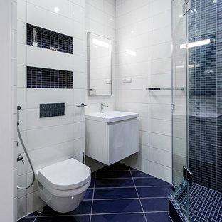 На фото: ванная комната в скандинавском стиле с плоскими фасадами, белыми фасадами, угловым душем, инсталляцией, синей плиткой, белой плиткой, плиткой мозаикой, белыми стенами, душевой кабиной, подвесной раковиной и душем с распашными дверями с