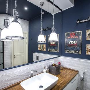 Bild på ett mellanstort funkis brun brunt badrum med dusch, med en dusch i en alkov, en vägghängd toalettstol, vit kakel, keramikplattor, blå väggar, klinkergolv i keramik, grått golv, dusch med gångjärnsdörr, släta luckor, vita skåp, ett fristående handfat och träbänkskiva