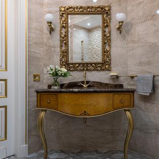 На фото: ванная комната среднего размера в викторианском стиле с фасадами островного типа, коричневыми фасадами, бежевой плиткой, плиткой из листового камня, консольной раковиной, серым полом и коричневой столешницей с