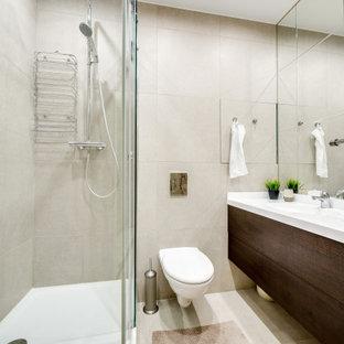 Стильный дизайн: ванная комната среднего размера в современном стиле с плоскими фасадами, темными деревянными фасадами, угловым душем, инсталляцией, бежевой плиткой, керамогранитной плиткой, полом из керамогранита, душевой кабиной, монолитной раковиной, бежевым полом, душем с распашными дверями и белой столешницей - последний тренд