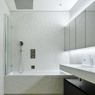 На фото: главные ванные комнаты в современном стиле с плоскими фасадами, черными фасадами, ванной в нише, душем над ванной, белой плиткой, монолитной раковиной, бежевым полом, белой столешницей, белыми стенами и душем с распашными дверями