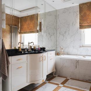 Пример оригинального дизайна: главная ванная комната в классическом стиле с бежевыми фасадами, белой плиткой, разноцветным полом, черной столешницей, фасадами с утопленной филенкой и ванной в нише