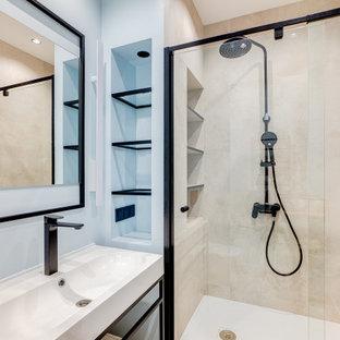 Пример оригинального дизайна: ванная комната в современном стиле с душевой кабиной, душем в нише, синими стенами, монолитной раковиной и душем с раздвижными дверями
